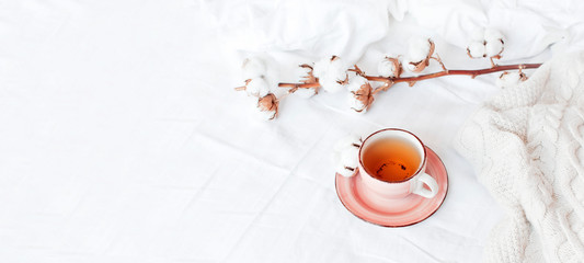 Cup of hot tea, branch of delicate cotton and knitted plaid sweater in bed with white linens. Cozy morning breakfast at home. Lifestyle gentle female background Copy Space autumn winter concept