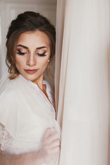 Gorgeous bride in silk robe holding stylish wedding dress in room in the morning. Happy sexy Bride and her beautiful wedding gown. Woman getting ready. Space for text