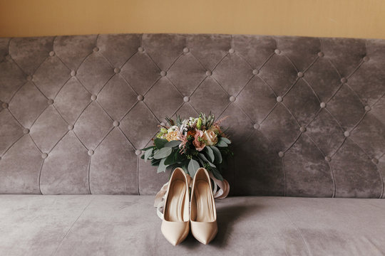 Modern wedding bouquet of pink roses and green eucalyptus with pink ribbons, beige shoes on stylish grey sofa. Contemporary composition of bridal accessory for wedding