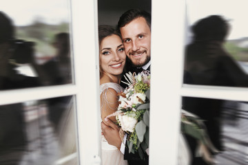 Gorgeous bride and stylish groom gently hugging at window. Happy wedding couple embracing and smiling. Romantic moments of newlyweds. Creative wedding photo. Copy space