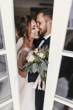 Gorgeous bride and stylish groom gently kissing at window. Happy wedding couple embracing. Romantic moments of newlyweds. Creative wedding photo through glass. Copy space