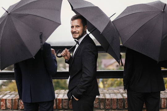 Stylish groom and groomsmen standing under black umbrella and posing. Confident man in suit holding umbrella in rainy outdoors. Rich Businessman. Finance wealth and business