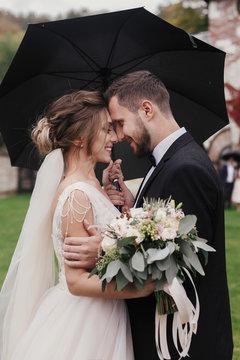 Gorgeous bride and stylish groom gently hugging under umbrella in rainy outdoors. Sensual wedding couple embracing. Romantic moments of newlyweds. Modern wedding photo