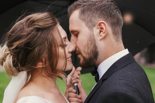 Gorgeous bride and stylish groom passionately kissing under umbrella in rainy outdoors. Sensual wedding couple embracing. Romantic moments of newlyweds. Modern wedding photo