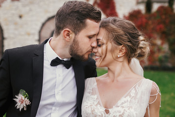 Gorgeous bride and stylish groom gently hugging and kissing outdoors. Sensual wedding couple embracing. Romantic moments of newlyweds. Wedding photo