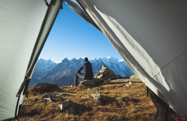 Hiker enjoying the mountain view in front of his tent. Chamonix, France.