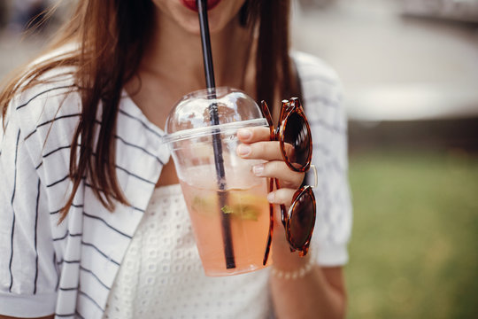 Ban single use plastic. Happy hipster girl  in retro dress, holding plastic cup and straw. Beautiful stylish young woman holding cold drink and relaxing in city street.