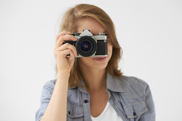 People, lifestyle and technology concept. Studio shot of stylish girl holding roll film camera at her face, taking picture of you. Young woman photographer using vintage device to take photo