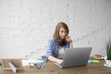 Job, occupation and electronic gadgets concept. Stylish young female working remotely on generic...