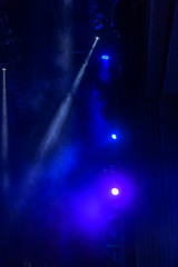 Stage lights. Several projectors in the dark. Multi-colored light beams from the stage spotlights on the stage in the smoke at the time of the entertainment show. Night club. Lights show. Lazer show