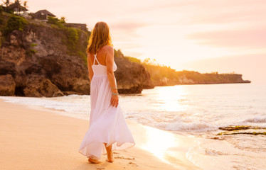 Carefree woman in white dress walking on the beach at sunset