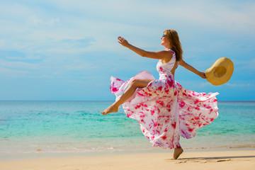 Happy woman making a big step forward on the beach