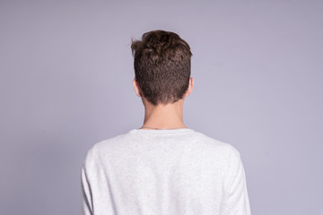 Back view of young man over gray background.