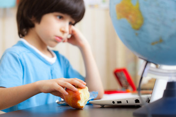 boy sitting with a laptop and eating apple