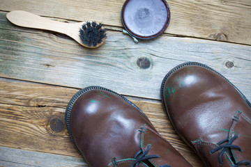 Still life with brown boots, shoe polish and shoe brush