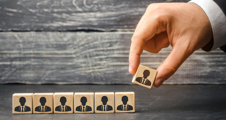 The leader builds team from cubes with employees. Businessman in search of new employees and specialists. personnel selection and management within the team. removes / dismisses the employee