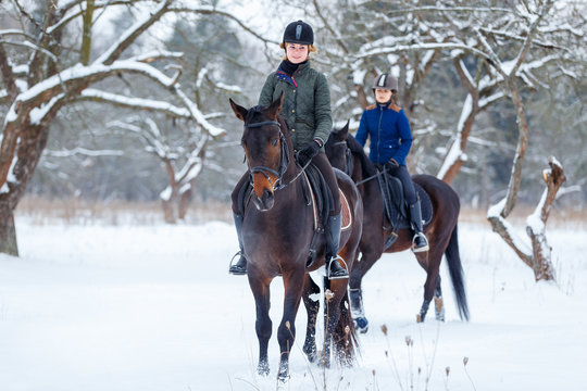 Two young women riding horses in winter park