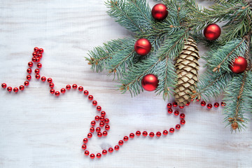Christmas tree branch with a bump on a white wooden background and red balls