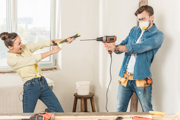 happy young couple having fun with tools during home improvement