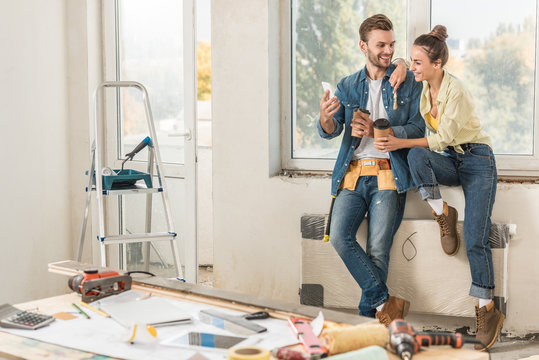 happy young couple holding paper cups and using smartphone repairment