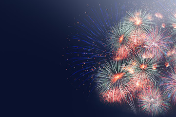 Colorful firework celebration..Fireworks displaying up in the sky over dark background with copy space .