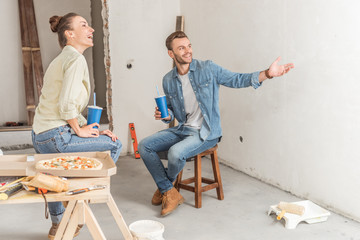 happy young couple holding paper cups and discussing repairment in new apartment