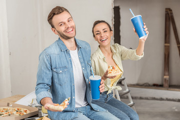 happy young couple holding paper cups with drinking straws and pizza slices during repairment in new house