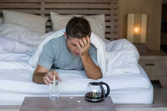 lifestyle home portrait of young exhausted and wasted man waking up suffering headache and hangover after drinking alcohol at night party lying on bed sick