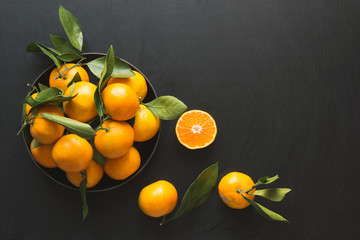Fresh mandarins with leaves in bowl on black. Healthy eating concept. Copy space.