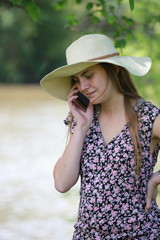 Young and pretty woman who is calling with her smartphone in a french park