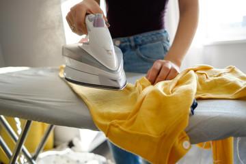 Fototapeta Girl ironing clothes  at home a yellow jacket obraz