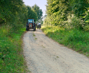 tractor in rural area, a tractor ride on a gravel road towards cyclists, tourists
