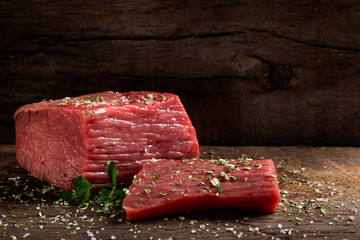 Raw beef meat with herbs on wood