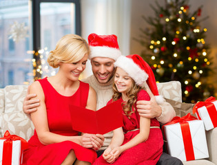 holidays, family and celebration concept - happy mother, father and daughter reading greeting card at home over christmas tree lights background
