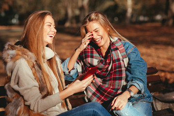 Two young women using smarthpone in the park and laughing