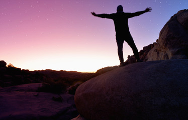 a person standing in a rocky landscape during sunset with stars in the sky