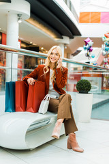 happy attractive woman talking on smartphone and sitting with shopping bags
