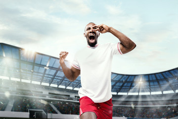 The football player in motion on the field of stadium