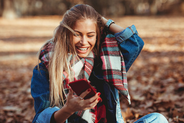 Young woman in the park using smartphone  and laughing
