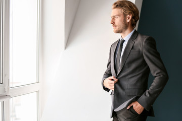 Thoughtful young businessman looking through window