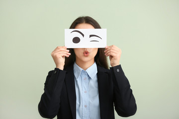 Emotional young woman hiding face behind sheet of paper with drawn eyes on light background