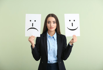 Young woman holding sheets of paper with drawn emoticons on light background