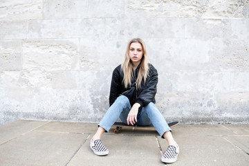 Teenage girl sitting on a skate board posing for a picture