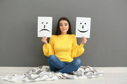 Emotional woman holding sheets of paper with drawn emoticons while sitting near grey wall