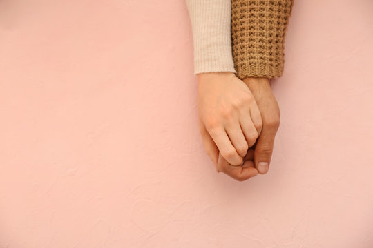 Loving young couple holding hands on color background