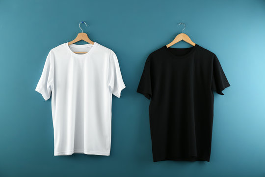 Hangers with blank t-shirts on color background