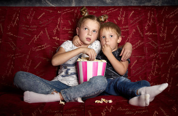 Children's cinema: A girl and a boy watch a movie at home on a big red sofa in the dark and eat popcorn.