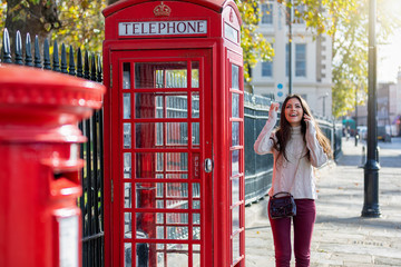 Touristin in London steht vor einer roten Telefonzelle und telefoniert mit ihrem Handy an einem sonnigen Herbsttag