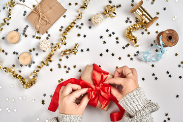 Female hands holding present with red bow on white background with delicate wavy ribbons and metallic star shaped confetti. Flat lay style
