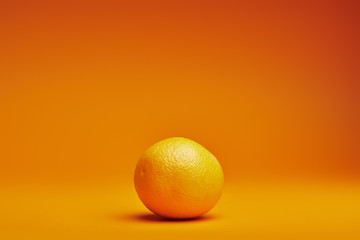 close-up view of fresh ripe whole orange on orange background Wall mural